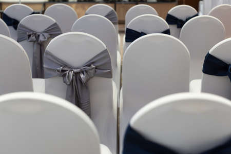 Wedding ceremony reception chairs in row decorated by ribbon. Imagens
