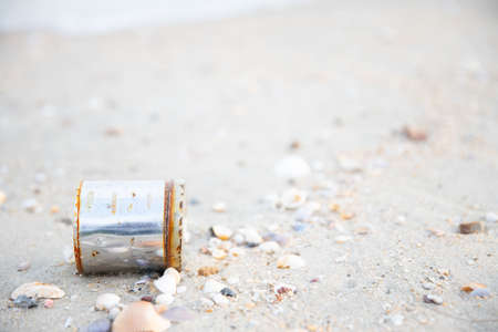 close up of silver metal can garbage on the beach with shell and sand. 스톡 콘텐츠