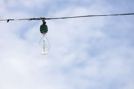 The outdoor old light bulb hanging on wire with blue sky background.