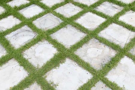 hoge hoekmening van vierkante rasterblok betonnen steen of marmeren tegel loopbrug stoep vloer met groen gras in de tuin, gebruik voor achtergrond en textuur. Stockfoto