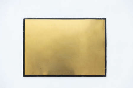 empty metallic golden plate sign with black border on white cement wall 版權商用圖片