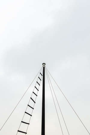 top of small ship masts in sky cloud background copy space with rope ladder used to observe from peak of the highest post.