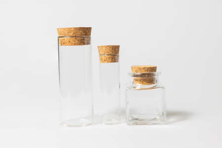 front view of transparent blank glass jar or test tube bottles with closed brown cork cap lids on white background Stock Photo
