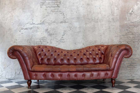 front view of luxury red genuine leather sofa on checkered pattern marble tiles floor with brick cement wall