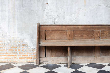front view of old wooden bench on checkered pattern marble tiles floor with brick and cement wall background in church