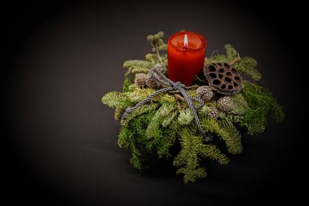Christmas red candle in a fir bouquet xmas decoration card. Imagens