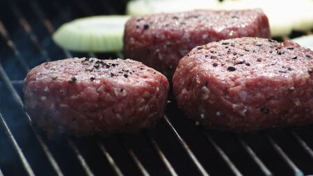 Raw Burger Patties On A Grill Ready To Be Grilled. Imagens