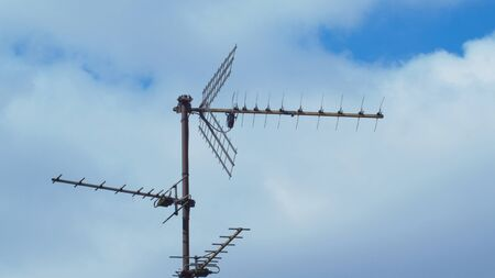 Old TV Receiver Antenna On A Roof Against Blue Sky. 写真素材