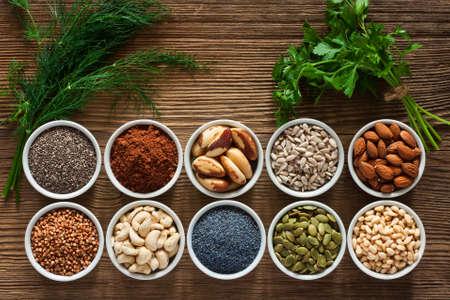 Alimentos ricos en magnesio como semillas de calabaza, semilla de amapola azul, anacardos, almendras, semillas de girasol, trigo sarraceno, cacao, chía, piñones, nueces de Brasil, hojas de perejil y eneldo. Foto de archivo