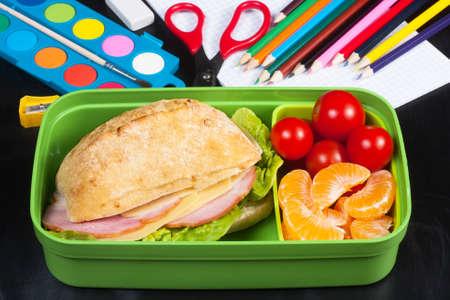 School lunch. Sandwich, small tomatoes, tangerine in plastic lunch box on black chalkboard.