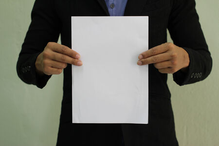 resignation: Business man holds paper with copy space  focus on hand holding paper   Stock Photo