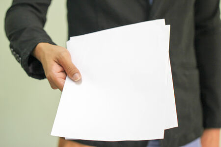 Business man holds paper with copy space  focus on hand holding paper   Stock Photo