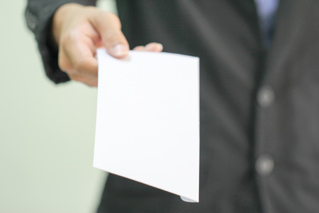 A businessman handing in a blank envelope  focus on hand holding envelope, other out of focus