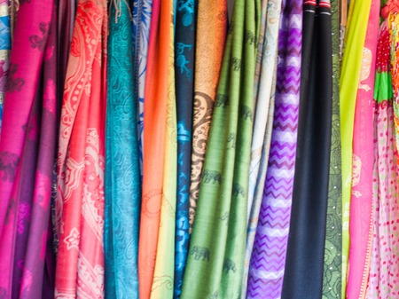 bazar: Rows of colourful silk scarfs hanging at a market stall in Rayong, Thailand Stock Photo
