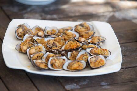 shellfish sea food in white plate on wood table 写真素材