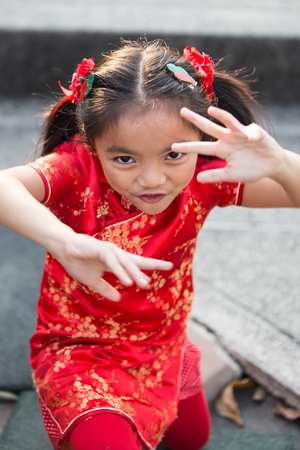 gung: Beautiful Asian kids girl with Chinese traditional dress Cheongsam ( Learn chinese martial art ) Stock Photo