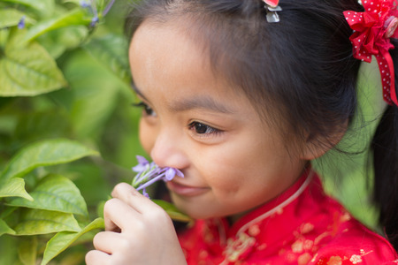 six year old: Portrait of a Six year old little girl outdoor in a garden smelling the flowers.
