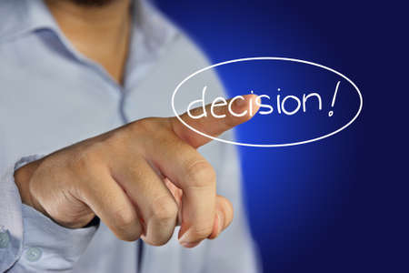 decision making: young men pointing his finger to click decision icon on virtual display Stock Photo