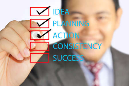 young businessman marks checking list of his business plan steps