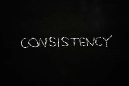 consistency: consistency word written with chalk on blackboard