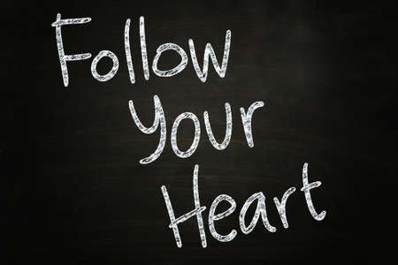 follow your heart quote written with chalk on blackboard photo