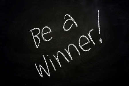 Motivational Phrase Be a Winner written with Chalk on Blackboard photo