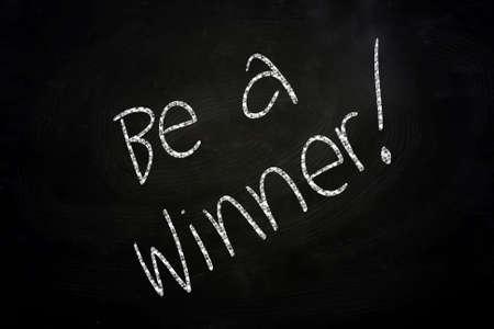 be the change: Motivational Phrase Be a Winner written with Chalk on Blackboard