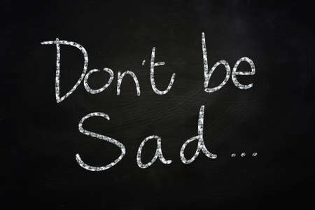 Dont be Sad, Motivational Phrase written on Blackboard photo