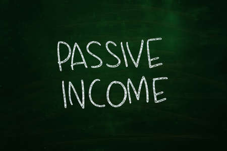 income market: Passive Income Lettering, written with Chalk on Blackboard
