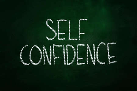 Self Confidence Lettering, written with Chalk on Blackboard photo