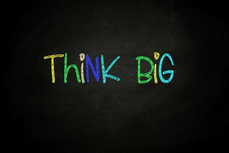 believe: Piensa en grande las letras, escrito con tiza de color en la pizarra