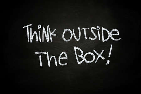 Think Outside The Box, written with Chalk on Blackboard photo
