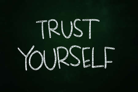 Trust Yourself Lettering, Motivational Phrase written with Chalk on Blackboard photo