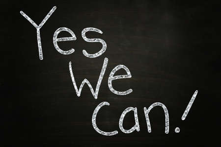 phrase: Yes We Can, Motivational Phrase written with Chalk on Blackboard