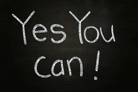 Yes You Can, Motivational Phrase written with Chalk on Blackboard