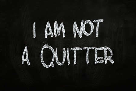 am: I am not a Quitter, Motivational Phrase written with Chalk on Blackboard