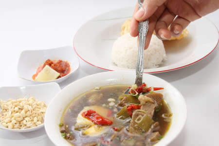 baby rice: Rawon or Indonesian beef black soup, served with white rice, baby bean sprouts, chili sauce and emping chips