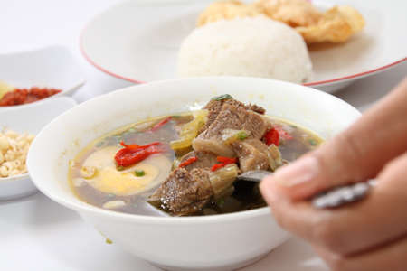 Rawon or Indonesian beef black soup, served with white rice, chili sauce and emping chips photo