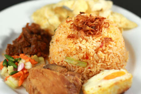 nasi: Fried rice or nasi goreng, served with fried chicken, egg , satay, pickles and chips Stock Photo