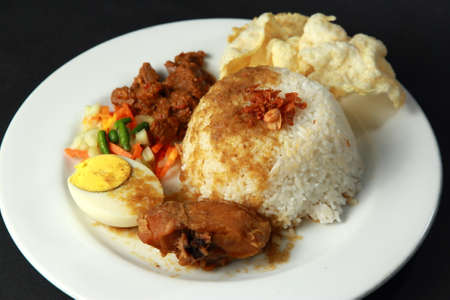 Indonesian mixed rice or nasi campur, served with fried chicken, boiled egg , satay, pickles and chips Stock Photo