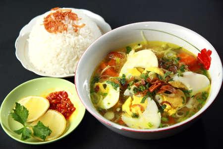 Indonesische kip soto of soto ayam, geserveerd met witte rijst en chili saus