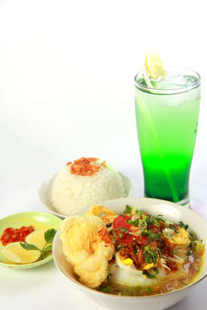 Indonesian chicken soto or soto ayam, served with white rice, chili sauce and a glass of lemonade photo