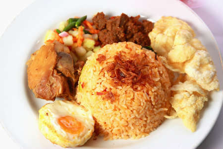 goreng: Fried rice or nasi goreng, served with fried chicken, egg , satay, pickles and chips Stock Photo