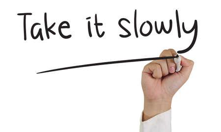 slowly: Imagen de un marcador de explotación de la mano y escribir tómalo con calma aislado en blanco