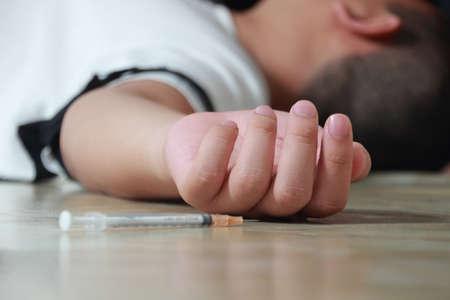 sobredosis: Adicto a las drogas Sobredosis acost� en el piso con una jeringa cerca de su mano Foto de archivo