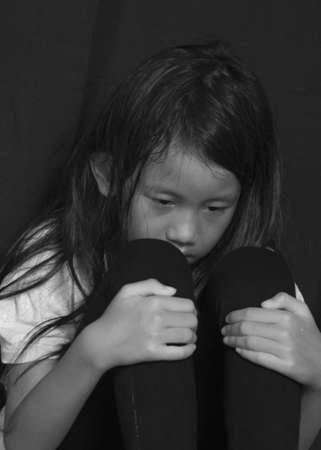 Little girl suffering bullying crying and hold her knees to her chest in black and white photo