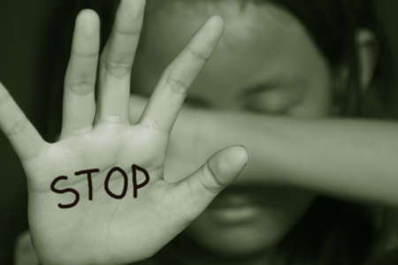 Little girl suffering bullying raises her palm asking to stop the violence in sepia color photo