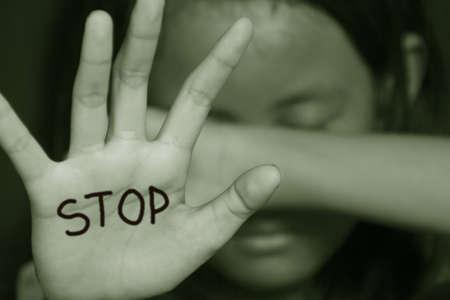 sexuel: Petite fille souffrances intimidation pose sa paume demandant d'arrêter la violence en couleur sépia