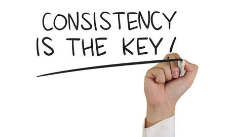 Business concept afbeelding van een hand die marker en schrijf Consistentie is de sleutel op wit wordt geïsoleerd Stockfoto