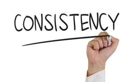 Business concept afbeelding van een hand die marker en schrijf Consistentie woord geïsoleerd op wit